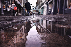 Puddle Reflection [15/366 2020] (_ _skdotcom_ _) Tags: puddle water rain street pavement path norwich bedford building people shop low pov perspective