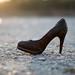 Thrown away high heeled shoe on the ground