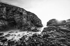 "long exposure of the sea coming amongst the rock of Aberdeenshire cliffs: Collieston, Aberdeenshire, Scotland. (grumpybaldprof) Tags: ""canon80d"" ""sigma1020mmf456dchsm"" ""wideangle"" ultrawide bw blackwhite ""blackwhite"" ""blackandwhite"" noireetblanc monochrome ""fineart"" ethereal striking artistic interpretation impressionist stylistic style contrast shadow bright dark black white illuminated mood moody atmosphere atmospheric ""longexposure"" ""neutraldensity"" nd landscape scenery vista collieston aberdeenshire scotland ""seacaves"" cliffs rocks sea waves ""northsea"" smugglers smuggling spirits sky clouds granite colliestonspeldings ""sundriedfish"" coves detail texture grey ""springsea"" foam movement seascape marine seaside seashore water 'cokinzproseriesnuancesextremefullnd'"