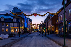 Main Street at Christmas (Arn_Thor) Tags: street city building road sky architecture house town urban evening downtown dusk outdoors sunset night outdoor travel neighbourhood urbanarea humansettlement clock person sign lighting neighborhood pavement walking red housing yellow tourism standing path light illuminated norway norge tromsø arctic winter snow ice icy pedestrian townsquare symmetry blue people christmas holidays