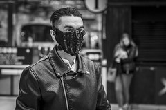 The Mask (Leanne Boulton) Tags: urban street candid portrait portraiture streetphotography candidstreetphotography candidportrait streetportrait streetlife man male face eyes expression mood emotion atmosphere slick hair leather jacket mask masked masquerade spikes intimidating scary weird odd unusual surreal commuter trainstation tone texture detail depthoffield bokeh naturallight indoor light shade city scene human life living humanity society culture lifestyle people canon canon5dmkiii 70mm ef2470mmf28liiusm black white blackwhite bw mono blackandwhite monochrome glasgow scotland uk