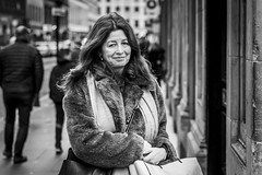 Flattered (Leanne Boulton) Tags: urban street candid portrait portraiture streetphotography candidstreetphotography candidportrait streetportrait eyecontact candideyecontact streetlife woman female lady face eyes expression mood emotion feeling smile smiling flattered reaction spontaneous fur furry coat cold winter weather style fashion tone texture detail depthoffield bokeh naturallight outdoor light shade city scene human life living humanity society culture lifestyle people canon canon5dmkiii 70mm ef2470mmf28liiusm black white blackwhite bw mono blackandwhite monochrome glasgow scotland uk