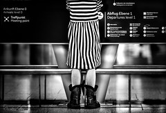 arrivals.&.departures.part.ii (grizzleur) Tags: street streetphotography candid candidphotography graphic graphical lines symmetry airport boots girl dress horizontals verticals diagonals arrival departure sony a7rii 135mm fe135mmf18gm sel135f18gm