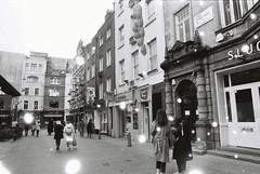 Lisle Street (Snovlox) (goodfella2459) Tags: nikonf4 revologsnovlox100 35mm blackandwhite film analog city london lislestreet buildings pedestrians streets bwfp