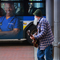 A Passing Glance (Ian Sane) Tags: ian sane images apassingglance man guitar performer busker musician bus advertisement picture candid street photography downtown portland oregon southwest 5th avenue morrison canon eos 5ds r camera ef24105mm f4l is ii usm lens