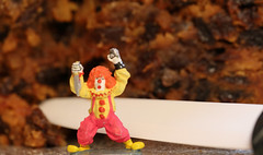 Macro Monday - Ceramic.  Crazy clown was determined to get the last slice of cake.  The person wielding the ceramic knife was equally as determined.  Who would be the winner?  IMG_1804 (alisonhalliday) Tags: clown cake miniature macromondays ceramic knife macro closeup food fruitcake canoneosrp canonef100mmf28lmacroisusm