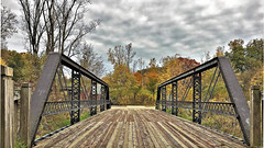 """Dead Bridge #1"" (Jan Nagalski) Tags: park bridge michigan unique odd restored restoration unusual battlecreek historicbridgepark historicbridge trussbridge bridgepark jannagal jannagalski autumn trees fall fallcolor darkclouds autumncolor wood steel perspective woodgrain lowangle er interes"