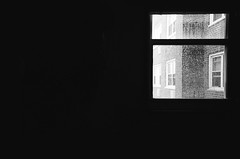 The View - City Living (Gabriella Ollandini) Tags: 35mm filmisnotdead filmphotography wit humour humor city urban window silhouette contrast analog analogue istillshootfilm hp5 ilford bw nyc manhattan urbanization commentary rain raindrops monochrome interior