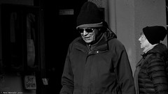 Beer Garden (Neil. Moralee) Tags: neilmoralee neilmpralee man woman couple married pair street candid old mature pub beer garden sign doorway dunster somerset uk people black white mono monochrome blackandwhite blackwhite neil moralee bw blackbackground olympus omd em5 cold hat coat winter bright shadow