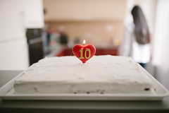 A white birtday cake with a lighet candle in it in shape of a heart with a number 10 on it with a woman and a room in the background (shixart1985) Tags: cake white candle display focus food hair heart light plate sugar tasty ten woman birthday love kitchen