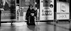Sitting in a railway station got a ticket... (Baz 120) Tags: candid candidstreet candidportrait city contrast street streetphoto streetcandid streetportrait strangers rome roma ricohgrii europe women monochrome monotone mono noiretblanc bw blackandwhite urban life portrait people provoke italy italia grittystreetphotography faces decisivemoment