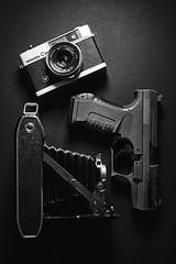 War and Peace (Paulie-W) Tags: gun pistol camera shooting cameras monochrome flickrfriday culture