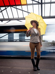 Naomi, Amsterdam 2019: Flashing by (mdiepraam) Tags: naomi amsterdam 2019 amsterdamcentraal portrait pretty attractive beautiful elegant classy gorgeous dutch blonde girl woman lady naturalglamour hat earrings umbrella boots jacket bus longexposure
