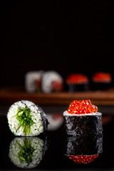 Set of sushi rolls on a black background. (Grandbarca) Tags: roll japan salmon sushi caviar fish expensive serving assorted japanese oriental red asian background healthy plate restaurant seafood board tradition soy set menu east ginger sauce wasabi sushiroll food dinner delicious spicy nutrition appetizer chopstick woodenboard redcaviar popular protein seaweed gourmet delicacy sushisticks
