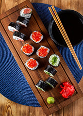A set of sushi rolls with red caviar, ginger and wasabi (Grandbarca) Tags: roll japan salmon sushi caviar fish expensive serving assorted japanese oriental red asian background healthy plate restaurant seafood board tradition soy set menu east ginger sauce wasabi sushiroll food dinner delicious spicy nutrition appetizer chopstick woodenboard redcaviar popular protein seaweed gourmet delicacy sushisticks