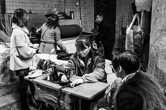 The tailor (Go-tea 郭天) Tags: chongqing républiquepopulairedechine women laidies tailor busy duty work working business sewing machine sew clothes table worker client customer cold winter workshop street urban city outside outdoor people candid bw bnw black white blackwhite blackandwhite monochrome naturallight natural light asia asian china chinese canon eos 100d 24mm prime group