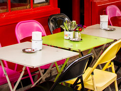 Coloured By Numbers? (Katrina Wright) Tags: france paris dsc55372 chairs empty cafe restaurant tables folding candles ashtrays cendriers cutlery window door red multicoloured line pattern happy wednesday