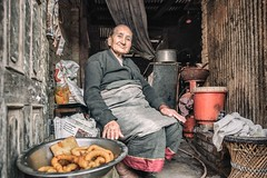 The Food Shopkeeper (Roberto Pazzi Photography) Tags: portrait city one person adult photography glance outdoor nikon namaste food shop sit woman street travel elder nepal full length asia bhaktapur culture place smile people human face nepalese door
