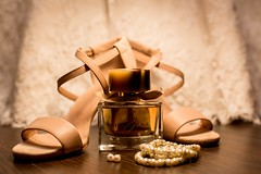 Brown glass fragrance bottle beside white pearl bracelets - Credit to https://homegets.com/ (davidstewartgets) Tags: accessories accessory blur bracelets closeup depth of field earrings ensemble fashion focus footwear heels high indoors jewelry party pearls perfume scent woman wooden flooring