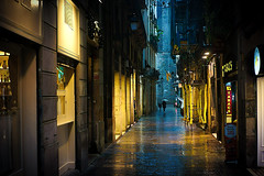 Sometimes it takes longer (Fnikos) Tags: street building architecture tower construction shop store light dark darkness shadow shadows rain lluvia umbrella paraguas water agua reflection people night nightview nightshot outside outdoor
