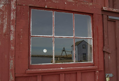 """Reflected """"Moon Rise"""" (brucetopher) Tags: window outsidelookingin view reflect reflection water sea ocean scene travel seethrough through lookingin porthole round glass glazing pier moonrise moon red motif motif1 motifno1 motifnumberone motifnumber1 one 1 shack shed lobstershack lobster harbor fisherman lobsterman house building architecture newengland rockport rockportharbor"""