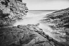 "Rocks and cliffs at 3 angles to cup the North Sea - Collieston, Aberdeenshire, Scotland. Black & white fine art. (grumpybaldprof) Tags: ""canon80d"" ""sigma1020mmf456dchsm"" ""wideangle"" ultrawide bw blackwhite ""blackwhite"" ""blackandwhite"" noireetblanc monochrome ""fineart"" ethereal striking artistic interpretation impressionist stylistic style mood calm peaceful tranquil restful ""neutraldensity"" 1024nd 10stop ""longexposure"" nd landscape scenery vista collieston aberdeenshire scotland ""seacaves"" cliffs rocks sea waves ""northsea"" smugglers smuggling spirits sky clouds granite colliestonspeldings ""sundriedfish"" coves detail texture grey moody ""springsea"" foam movement seascape marine seaside seashore water"