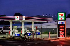Push Bike Rider (Erich Schieber) Tags: australia orange people petrolstation night urban sign