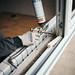 Fenstermonteur dichtet ein Fenster mit Polyurethanschaumstoff ab