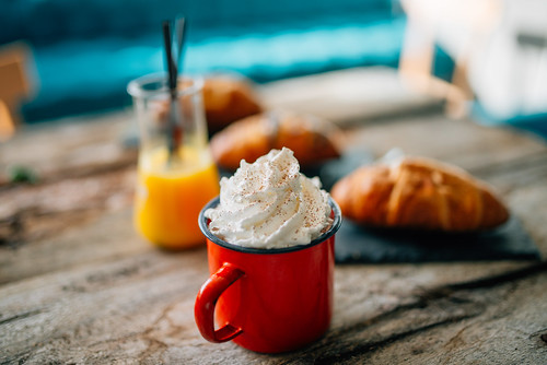 Cup of whipped cream with sprinkles with an orange juice glass and three croissants behind it displayed on a table