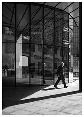 Turning a Corner (Dave Button) Tags: fuji fujifilm bw blackandwhite mono monochrome border tones shadows person people street view photo shade grey gray city light sunlight building urban space lines london cityoflondon glass reflection pillar window xe2s 27mm