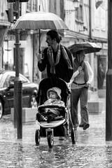 Dad keeps it dry! (lumafoto - luc bauwens) Tags: blackwhite street rain umbrella child man regen kind paraplu streetphoto
