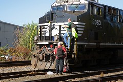 Norfolk Southern Railroad GE ES44AC locomotive # 8063 is seen with the cab crew boarding the engine in a small yard in Johnson City, Tennessee 10-3-2017 (alcomike43) Tags: norfolksouthernrailroad johnsoncitytennessee city yard railroads trains freighttrains crewmen personnel employees cabcrew engineer conductor tracks ballast roadbed rightofway rails ties siding mainline jointedsectionrail weldedribbonrail anglebars tieplates spikes switch turnout locomotive engine diesel ge es44ac dieselengine diesellocomotive dieselelectriclocomotive 8063 buildings railroadfacility photo photograph color digitalimage