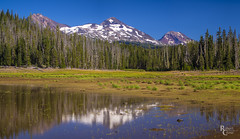 The Three Sisters at Hand Lake (RobertCross1 (off and on)) Tags: 40150mmf456mzuiko cascaderange cascades em5 handlake lane mckenziepass omd or olympus oregon pacificnorthwest threesisters threesisterswilderness bluesky forest glacier lake landscape mirrorless mountains panorama reflection snow trees volcanic volcano water