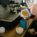 Milk being poured into espresso cup of coffee, next to the coffee maker