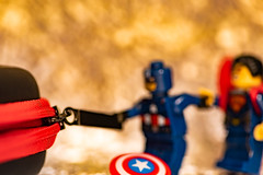 Pulling Power.... (Aleem Yousaf) Tags: nikon d850 nikkor105mm bokeh macro closeup shallow depth field tabletop light studio photography creative flickr macromondays zipper protection case candle lit super hero lego captain america man mini figures pulling power