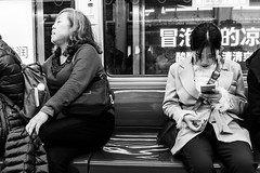 We belong to different worlds (Go-tea 郭天) Tags: chongqing républiquepopulairedechine women laides young old generation metro busy chat chatting virtual real friends ignorance mobile phone cellular cell cellphone data network connected connexion coach bench seated sit commuters passengers travelers 2 street urban city people candid bw bnw black white blackwhite blackandwhite monochrome naturallight natural light asia asian china chinese canon eos 100d 24mm prime inside indoors subway