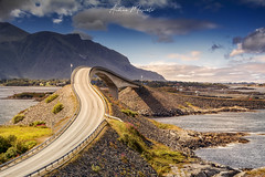 Storseisundet Bridge - Atlantic Ocean Road (Norway) (Andrea Moscato) Tags: andreamoscato norvegia norge bokmål nynorsk north europe view vivid vista day light luce shadow ombre blue white red yellow history historic cielo sky art artist clouds nature natura nuvole natural naturale mountain montagna landscape sun ponte bridge street strada road structure architecture fence perspective water stones rock green tourist attraction