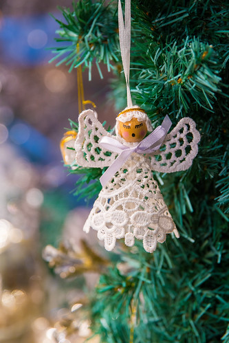 Little angel decoration hanging on a Christmas tree