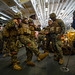 U.S. Marines rain to carry an injured squad mate in the hangar bay of amphibious assault ship USS America