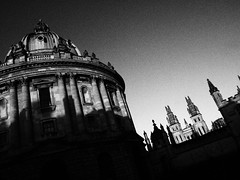 Radcliffe Camera and Hartford College (cycle.nut66) Tags: blackandwhite monochrome grayscale grainy film art filter stone stonework old buildings oxford university towers spires sky gradation olympus epl1 micro four thirds mzuiko 1442