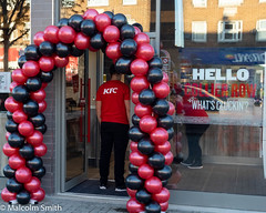 KFC Opens Today (M C Smith) Tags: pentax k3 balloons red black new shop kentuckyfriedchicken collierrow essex reflections letters symbols arch people doorway mat tree buildings blue yellow white staff uniform standing bending food
