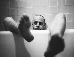 Bath Time (Gabriella Ollandini) Tags: portrait bath tub private candid man guy feet head 35mm filmisnotdead filmcamera filmphotography filmnegative ilford istillshootfilm shadows contrast vintage retro analog analogica analogue human legs people mature bwfp framed bathroom ricoh kr5