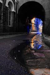 Bleu poterne ! (Tonton Gilles) Tags: alençon normandie heure bleue pose longue mise en scène caniveau ras du sol personnage écharpe chapeau passage de la poterne rue reflets flaque deau eau réverbères lampadaires jaune bleu noir et blanc partiel paysage urbain