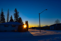 Setting between the two (darletts56) Tags: sky blue sun sunset white yellow gold golden orange snow tree trees home homes house houses pole poles lamp lamps wire wires line lines road roads vehicle vehicles village saskatchewan canada reflection dusk evening sundown shadow shadows