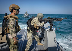 Electronics Technician 2nd Class Zac Colasanto observes Master-at-Arms 2nd Class Sydney Gass, assigned to Naval Security Force Harbor Patrol Unit Bahrain during an M-240B machine gun qualification exercise.