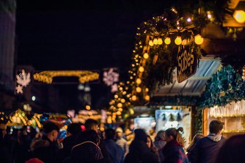 Menschen, Lichter und Süßes an einem Weihnachtsmarkt