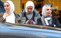 `2867` (roll the dice) Tags: london westminster w1 westend sad fun funny people reaction three muslim headscarf traffic blur crossing streetphotography pretty sexy girls faces sunglasses mobile phone classic uk art england urban unaware unknown fashion culture portrait strangers candid canon tourism tourists selfridges shopping natural mouth window reflection scarf cold