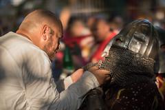 Knappe hilft dem Ritter sein Helm anzuziehen
