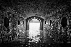 In the Dock (Ffotograffiaeth Dylan Arnold Photography) Tags: monochrome blackandwhite bricks roof walls dock portholes circles black opening sea outdoors indoors inside outside white texture vaulted structure water stone contrast symmetry symmetrical arch archway victorian fineart wales cymru bay launch boathouse dark light shadows ripples wet dank wall
