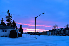 Bright pink and yellow sunset (darletts56) Tags: sky blue cloud clouds pink purple yellow white brown green pole poles lamp light lights house houses home homes snow tree trees vehicle vehicles village saskatchewan canada praqirie country countryside truck highway passing through wire wires line lines power road roads trucks semi transport
